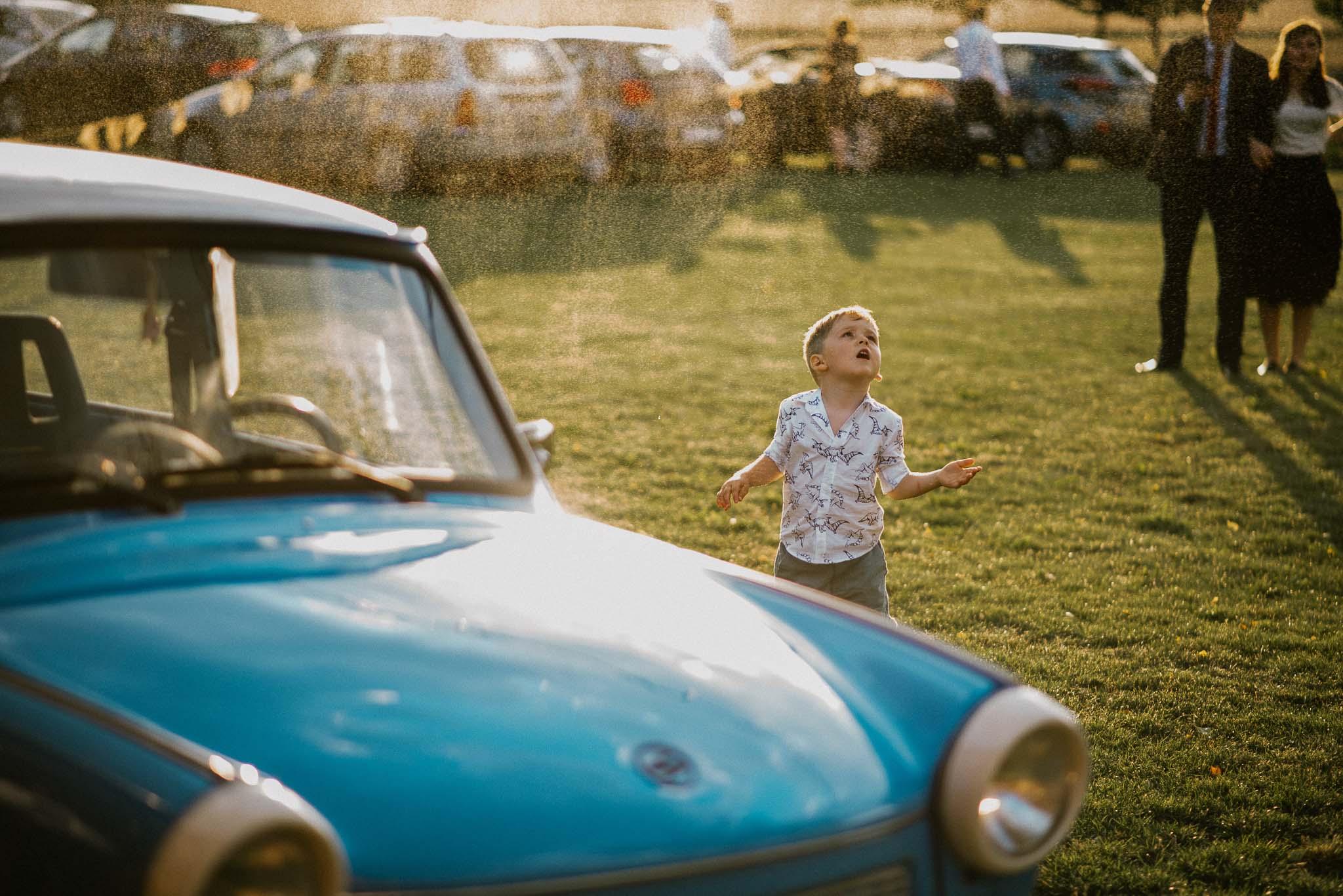 Chłopiec przy starym niebieskim trabancie - ślub w stodole Dyrkowo