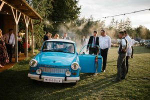 Goście weselni przy starym niebieskim trabancie - ślub w stodole Dyrkowo