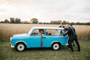 Goście weselny pchają starego, niebieskiego trabanta z parą młodą - ślub w stodole Dyrkowo Sesja ślubna z trabantem