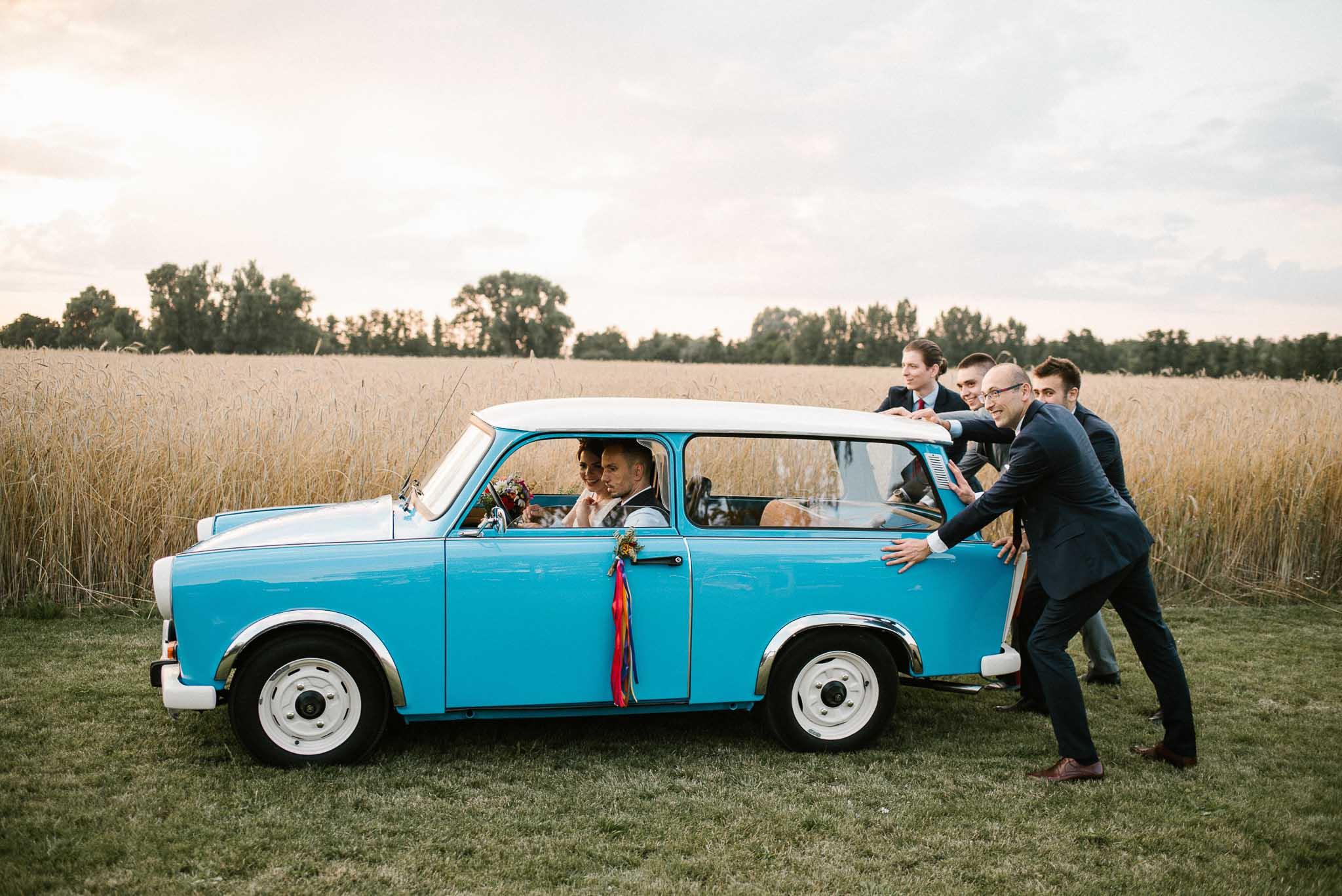 Goście weselny pchają starego, niebieskiego trabanta z parą młodą - ślub w stodole Dyrkowo