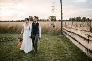Para młoda idzie trzymając się za ręce - sesja ślubna w plenerze w Dyrkowie przy stodole