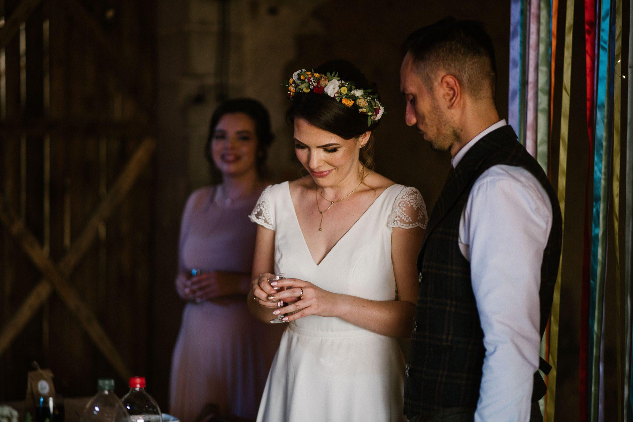 Para młoda wznosi toast w stodole - sesja ślubna w stodole Dyrkowie