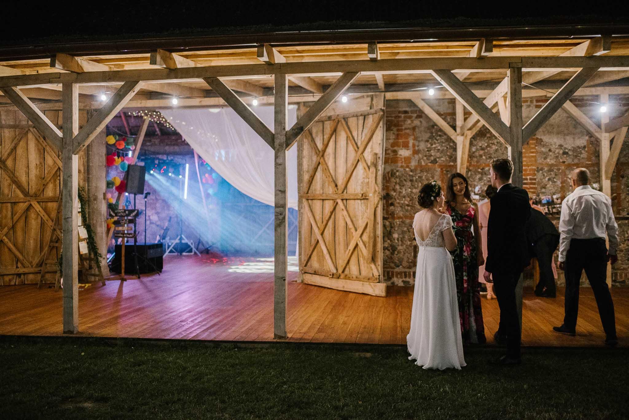 Para młoda z gośćmi przed stodołą - ślub w stodole Dyrkowo