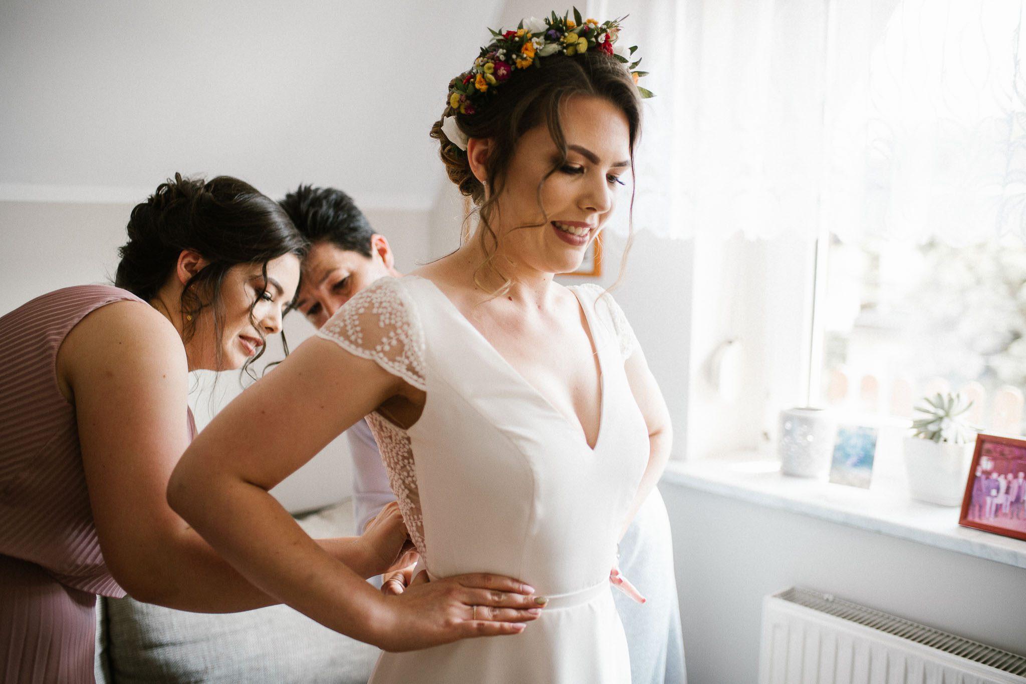 Panna młoda zakłada suknię ślubną - ślub w stodole w Dyrkowie