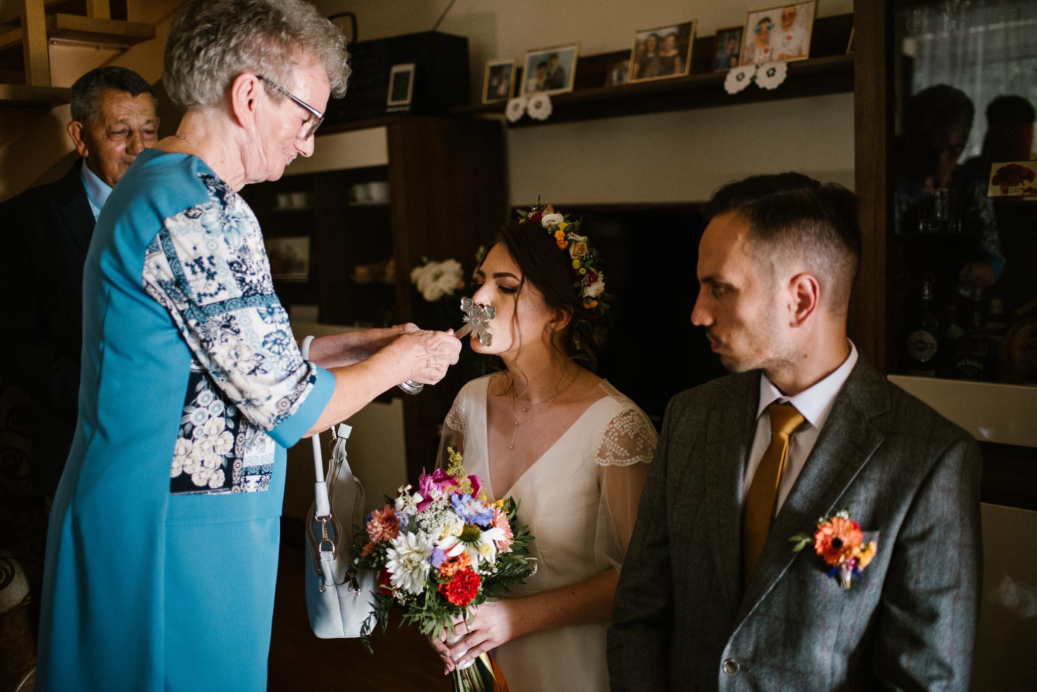 Panna młoda i pan młody podczas błogosławieństwa rodziców - ślub w stodole Dyrkowo