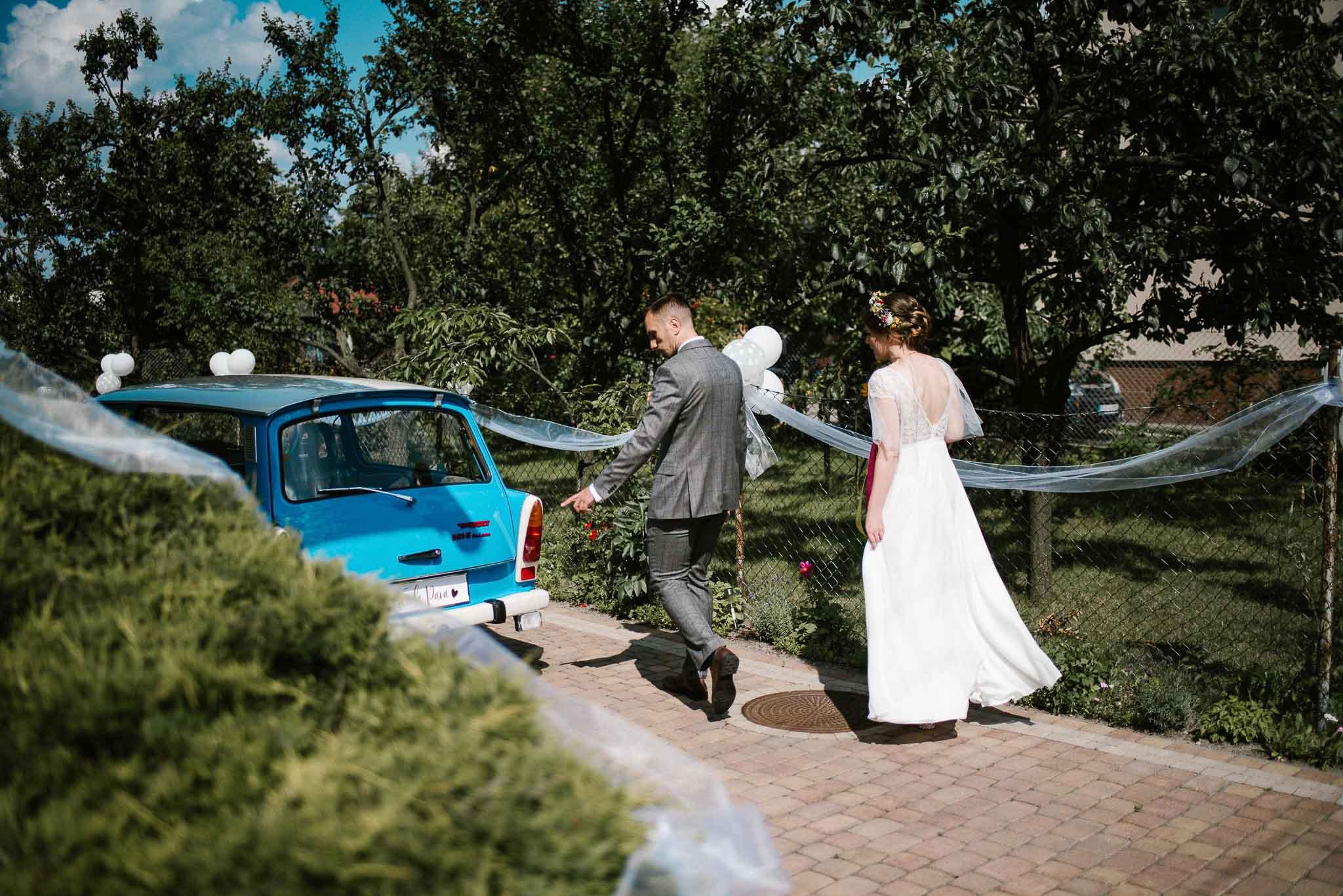 Państwo młodzi wsiadają do starego, niebieskiego trabanta - ślub w stodole Dyrkowo