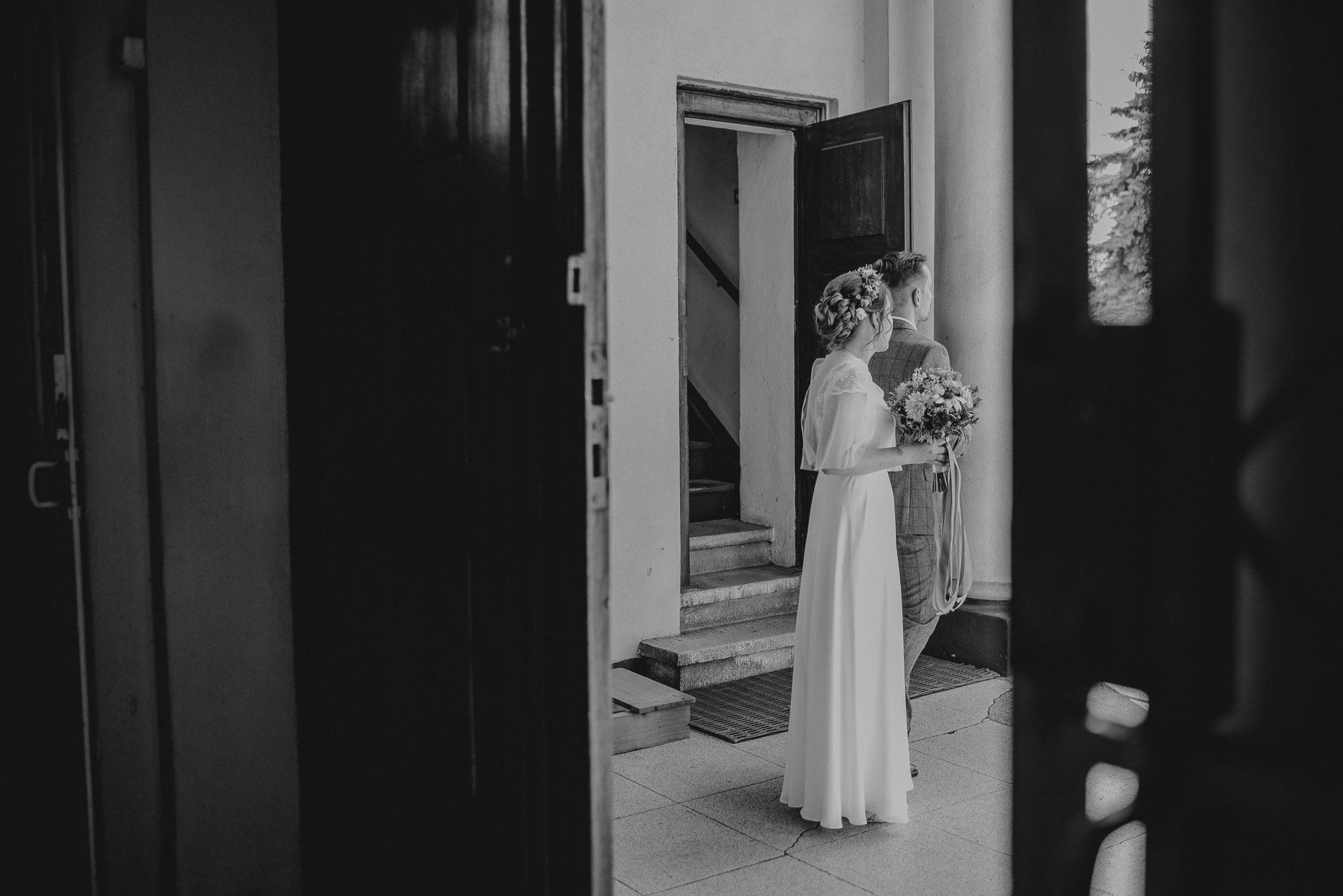 Para młoda stoi przed kościołem - ślub w stodole Dyrkowo