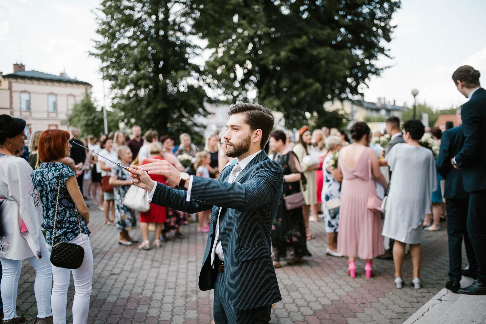 Dyrygent przed kościołem - ślub w stodole w Dyrkowie