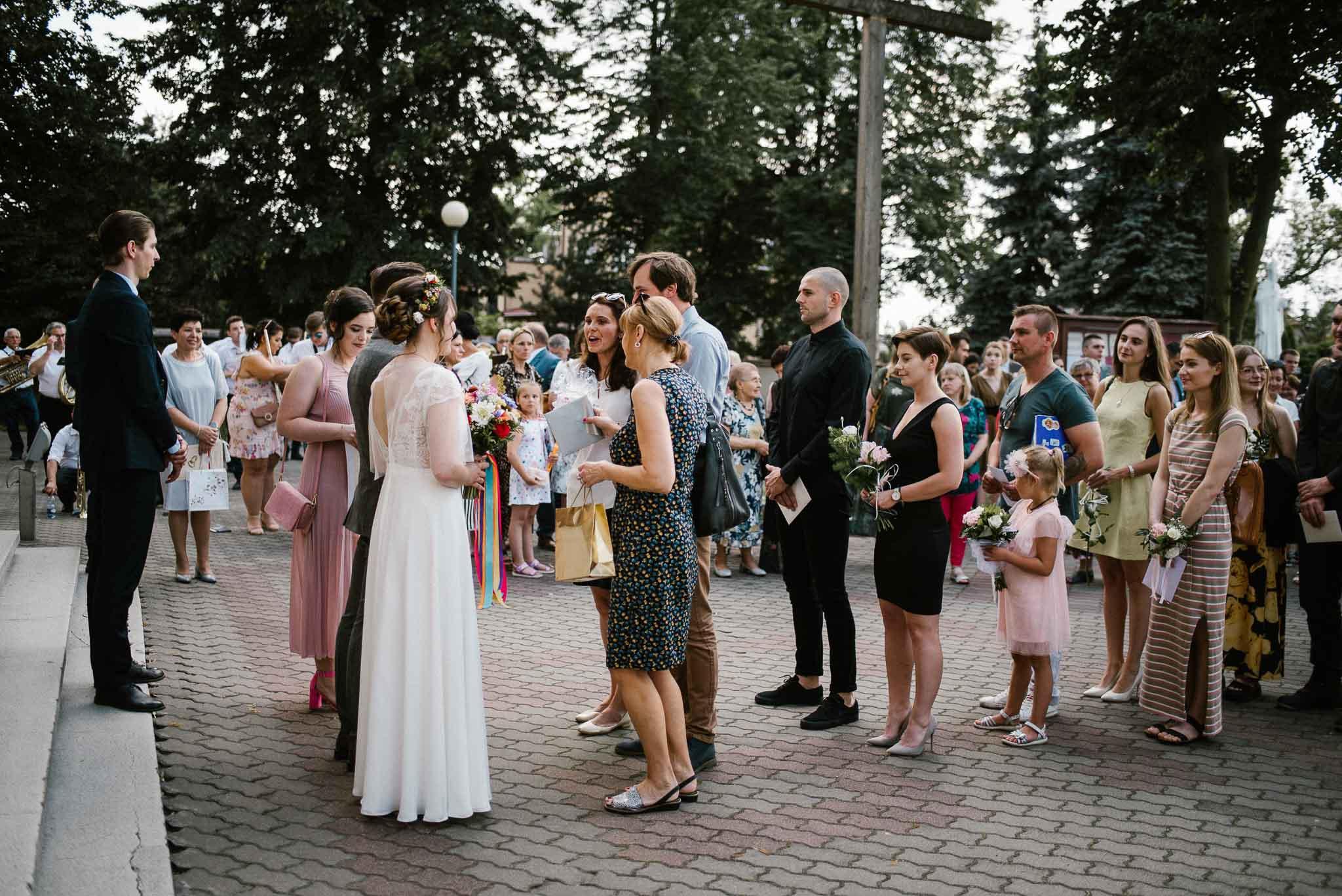 Goście zgromadzeni pod kościołem - ślub w stodole w Dyrkowie