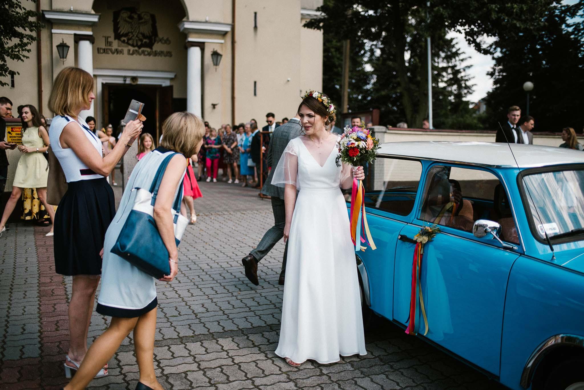 Panna młoda wchodzi do niebieskiego trabanta - ślub w stodole Dyrkowo