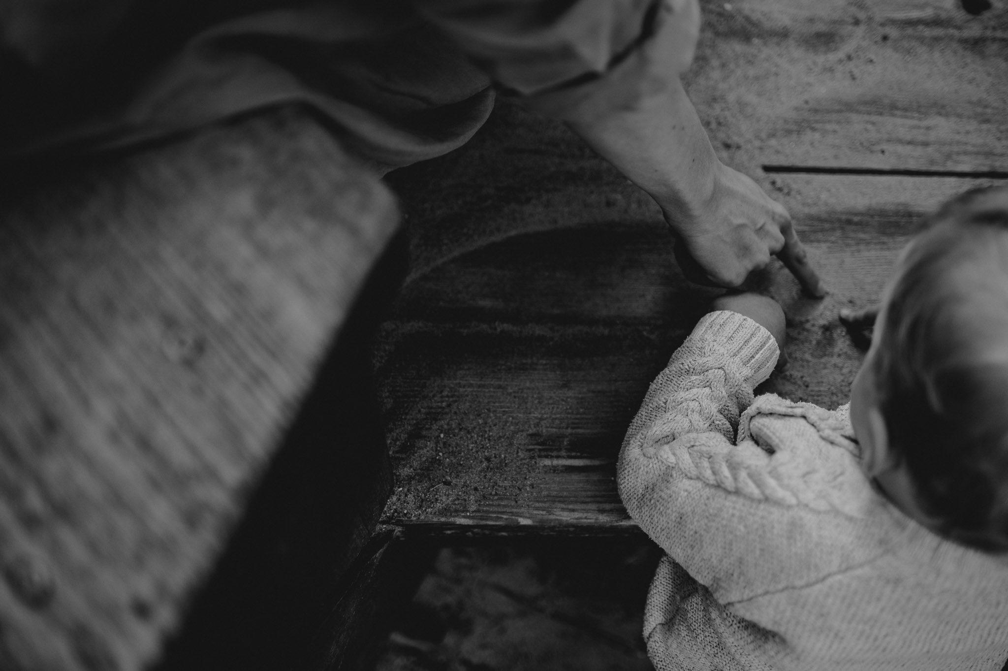 rączka dziecka oparta o drewnianą deskę - sesja rodzinna w plenerze jesienna Poznań