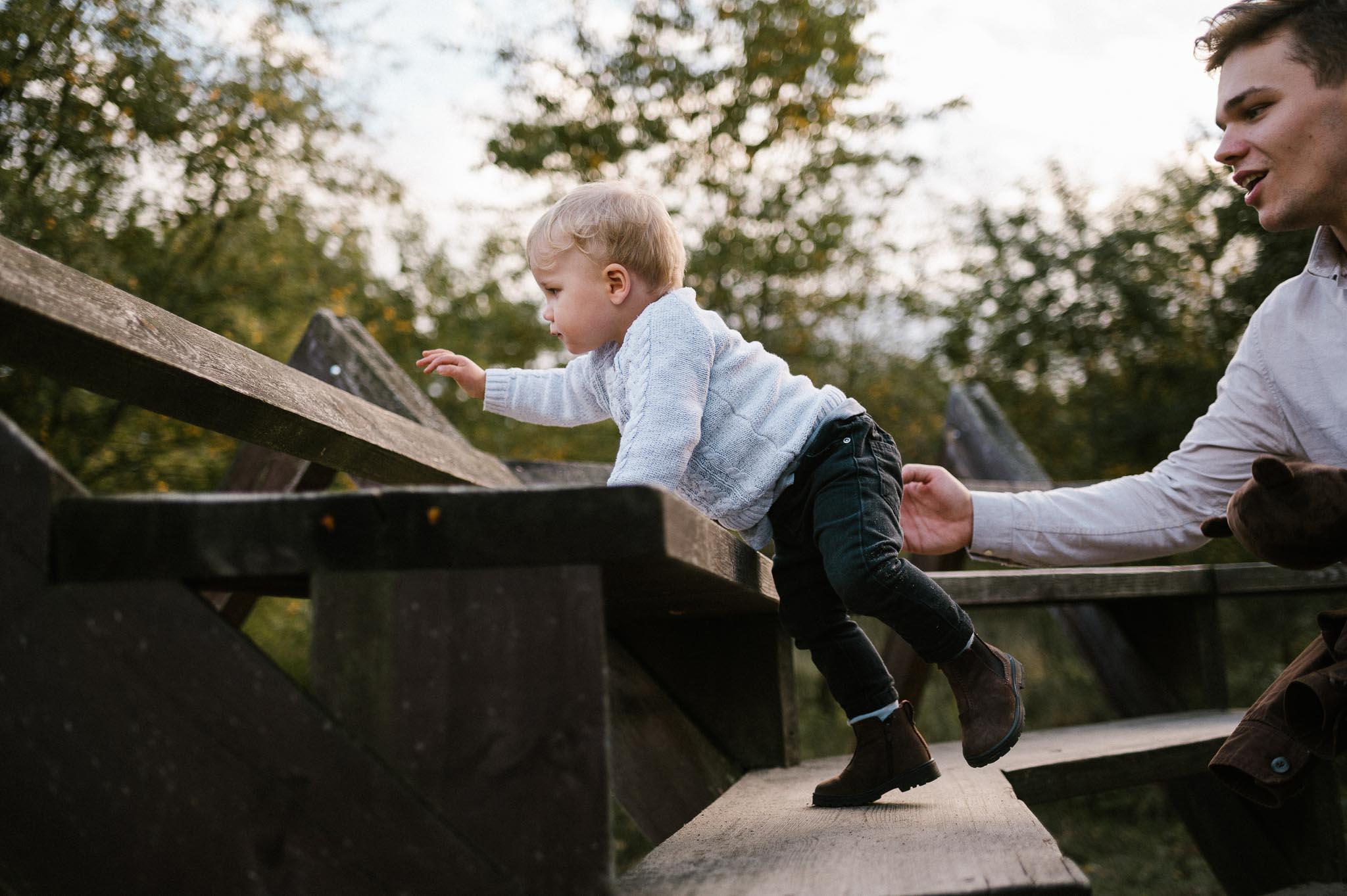 Tata trzyma synka, który wspina się na drewnianą konstrukcję  sesja rodzinna w plenerze jesienna Poznań