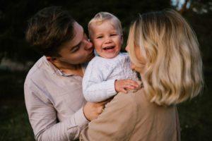 Rodzice trzymają synka na rękach - jesienna sesja rodzinna w plenerze Poznań