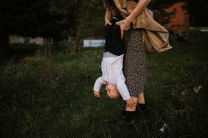 Mama trzyma synka na rękach i kręci nim dookoła - sesja w plenerze jesienią w Poznaniu