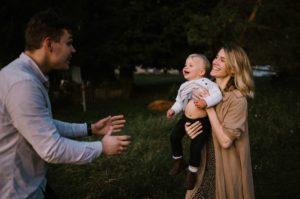 Mama trzyma synka na rękach i podaje tacie - sesja w plenerze jesienią w Poznaniu