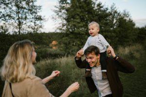 Tata trzyma malucha na barana o podbiega do mamy - Jesienna sesja rodzinna w plenerze Poznań