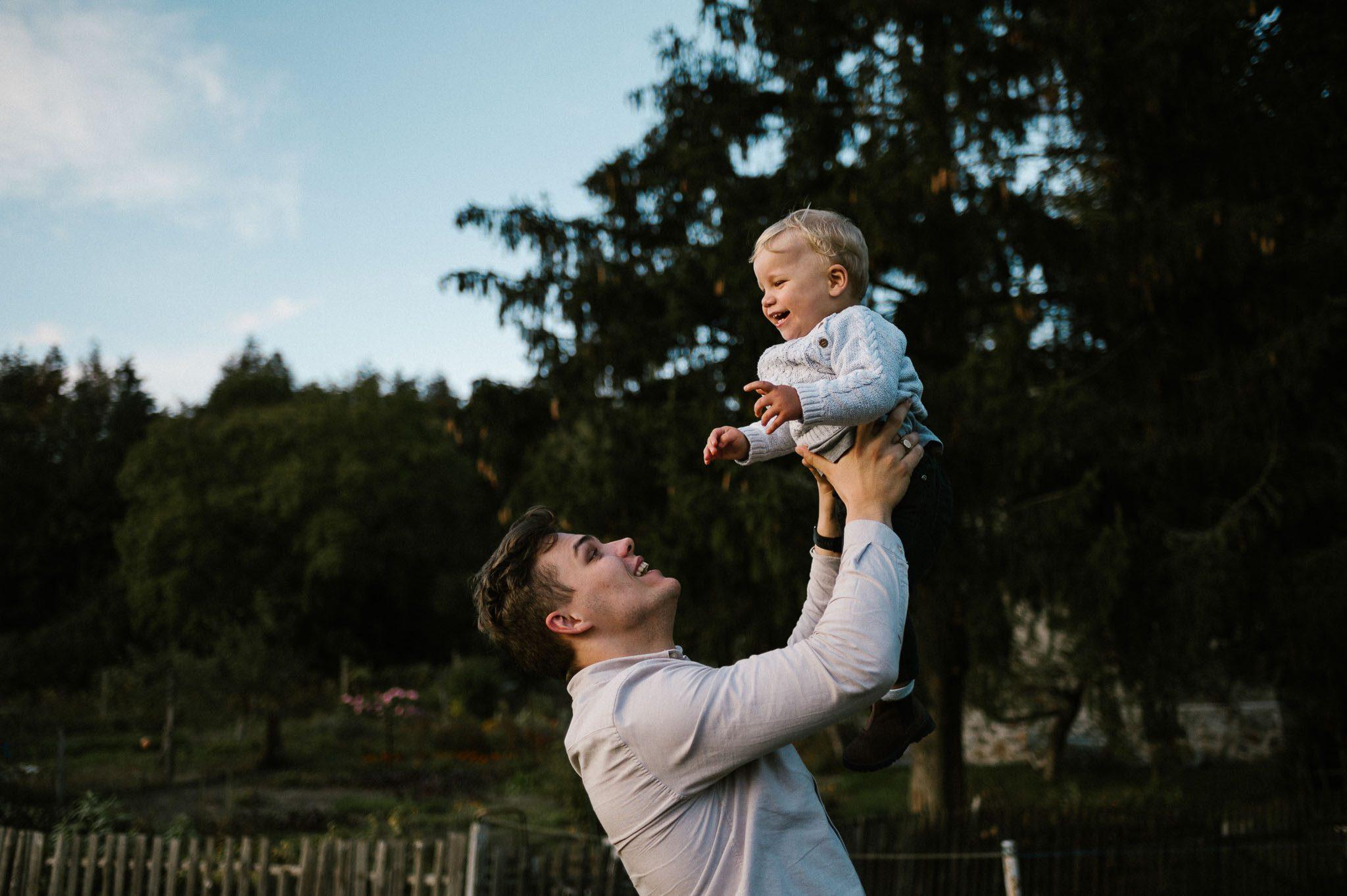 Mama trzyma synka na rękach i podrzuca do góry - sesja w plenerze jesienią w Poznaniu