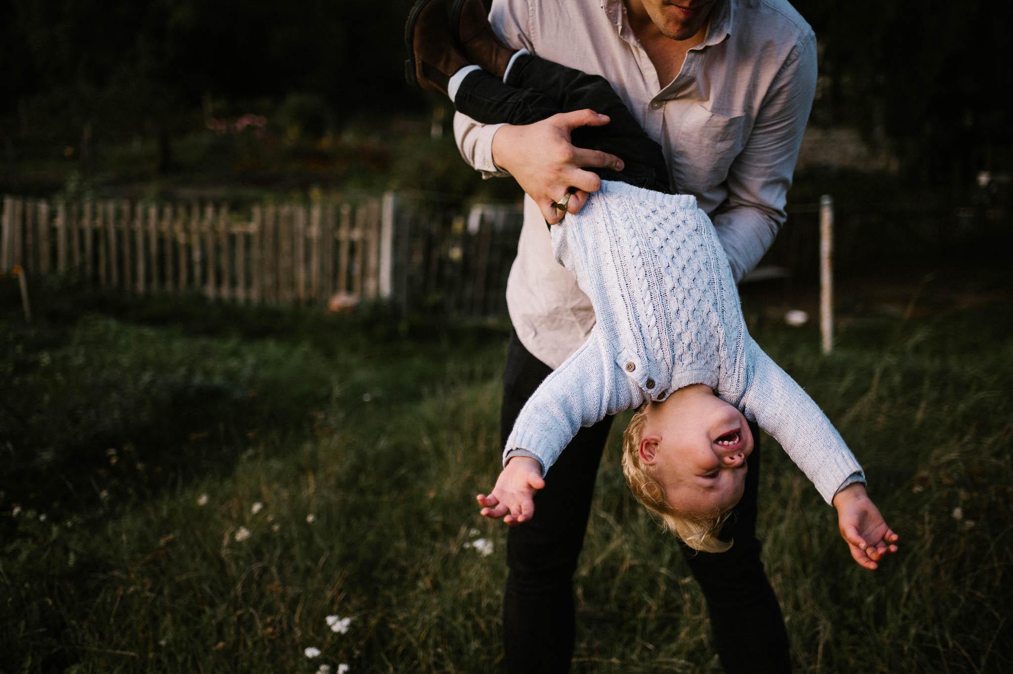 Tata trzyma synka na rękach i kręci nim dookoła - sesja w plenerze jesienią w Poznaniu