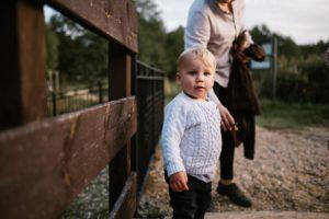 Chłopiec stoi i patrzy w obiektyw - jesienna sesja rodzinna w plenerze Poznań
