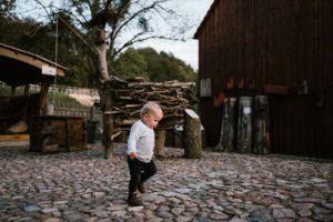 Chłopiec idzie sam po kostce brukowej - jesienna sesja rodzinna w plenerze Poznań