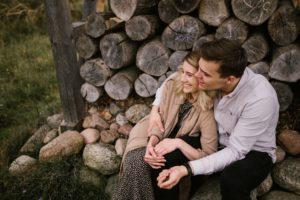 Mama i tata siedzą przy belkach drewnianych i się przytulają - jesienna sesja rodzinna w plenerze Poznań