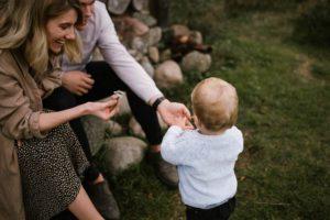 Chłopiec daje rodzicom kwiatek - jesienna sesja rodzinna w plenerze Poznań