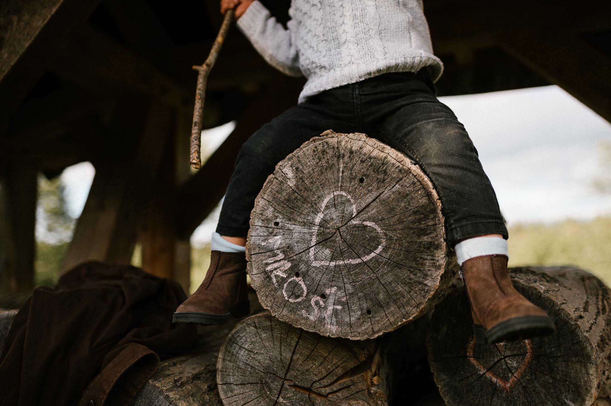 Napis miłość na drewnianych palach - jesienna sesja rodzinna w plenerze Poznań