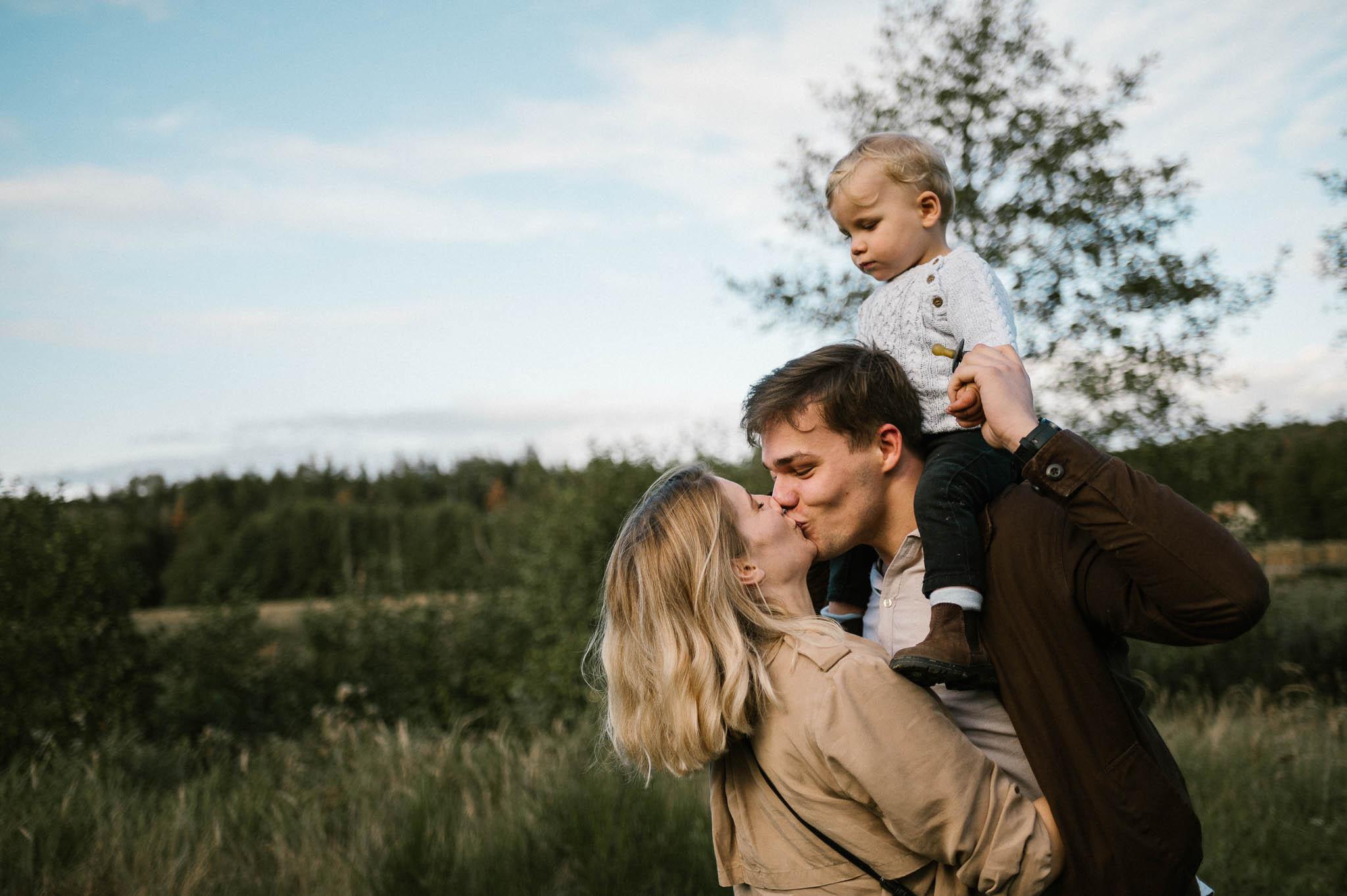 Tata trzyma syna na barana i daje buziaka mamie - Jesienna sesja rodzinna w plenerze Poznań