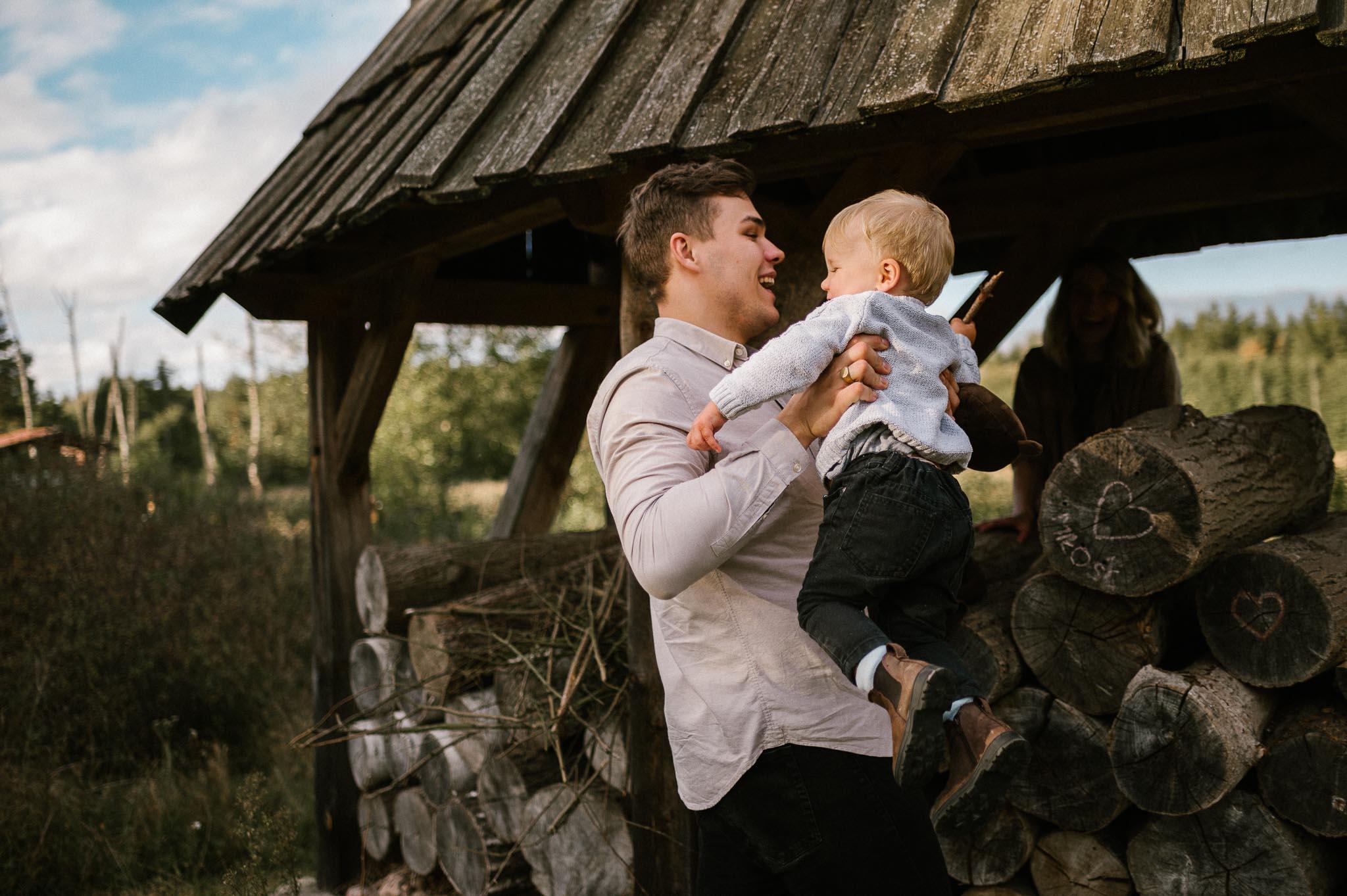 Tata trzyma synka na rękach - jesienna sesja rodzinna w plenerze Poznań