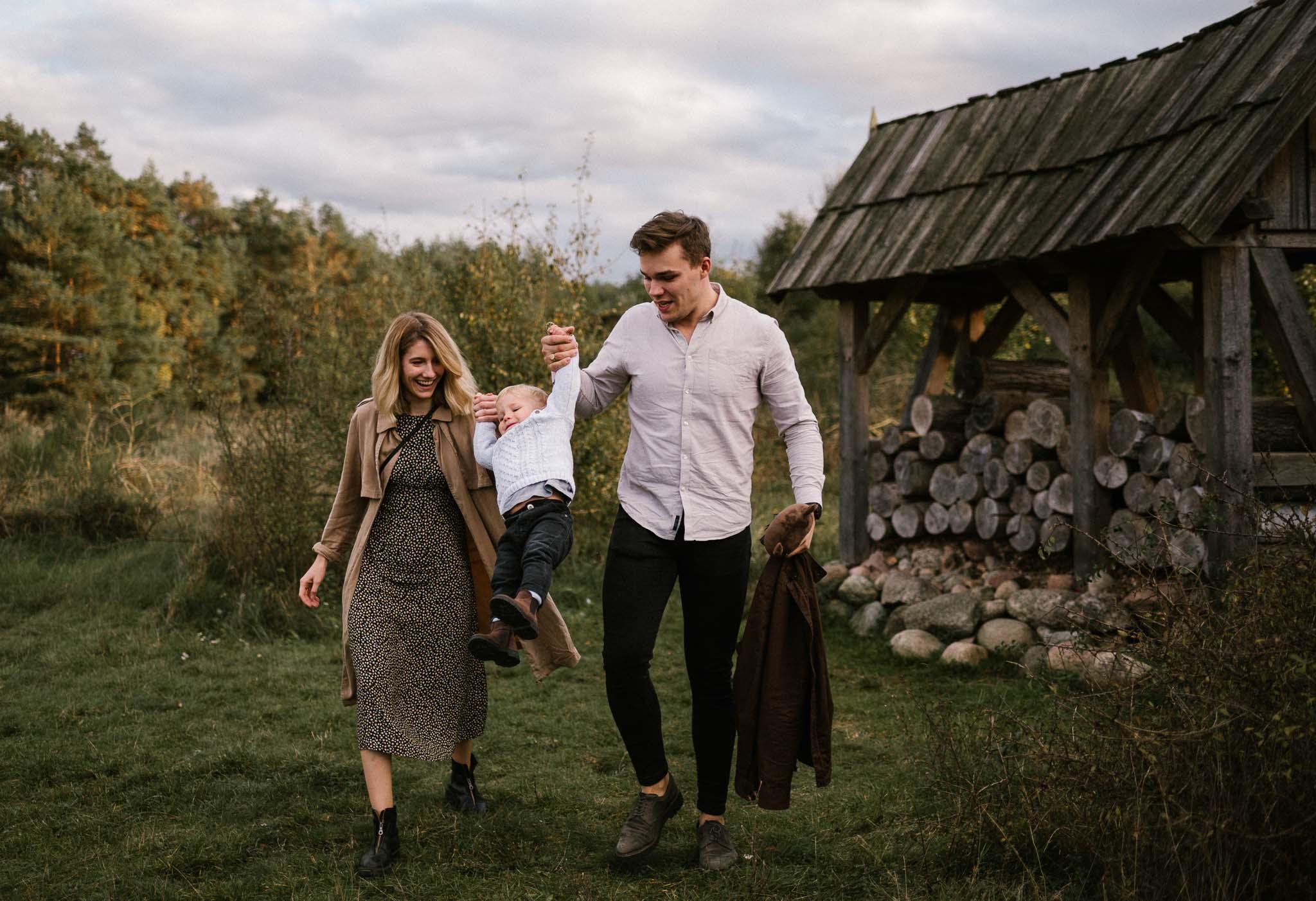mama i tata trzymają synka za ręce i podrzucają do góry - jesienna sesja rodzinna w plenerze Poznań