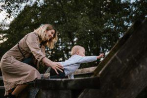 Mama trzyma synka, który wspina się na drewnianą konstrukcję sesja rodzinna w plenerze jesienna Poznań