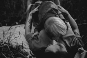 Synek przytula się do mamy i ciążowego brzuszka - Sesja ciążowa na łące w plenerze Poznań