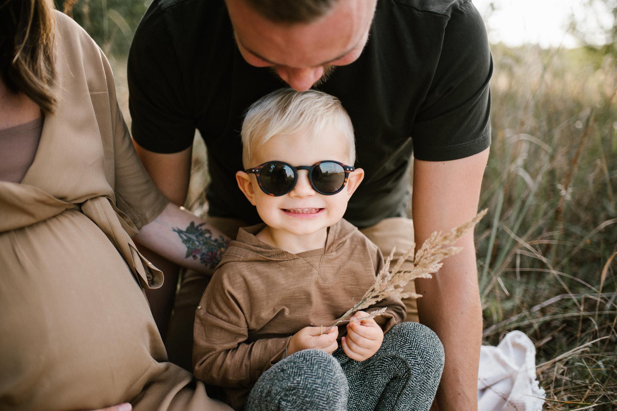 Chłopiec w okularach przeciwsłonecznych - Sesja ciążowa na łące w plenerze Poznań
