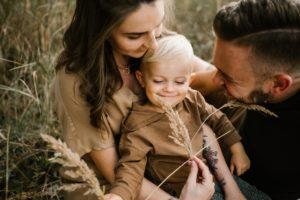 Rodzice bawią się z synkiem trawą - Sesja ciążowa na łące w plenerze Poznań