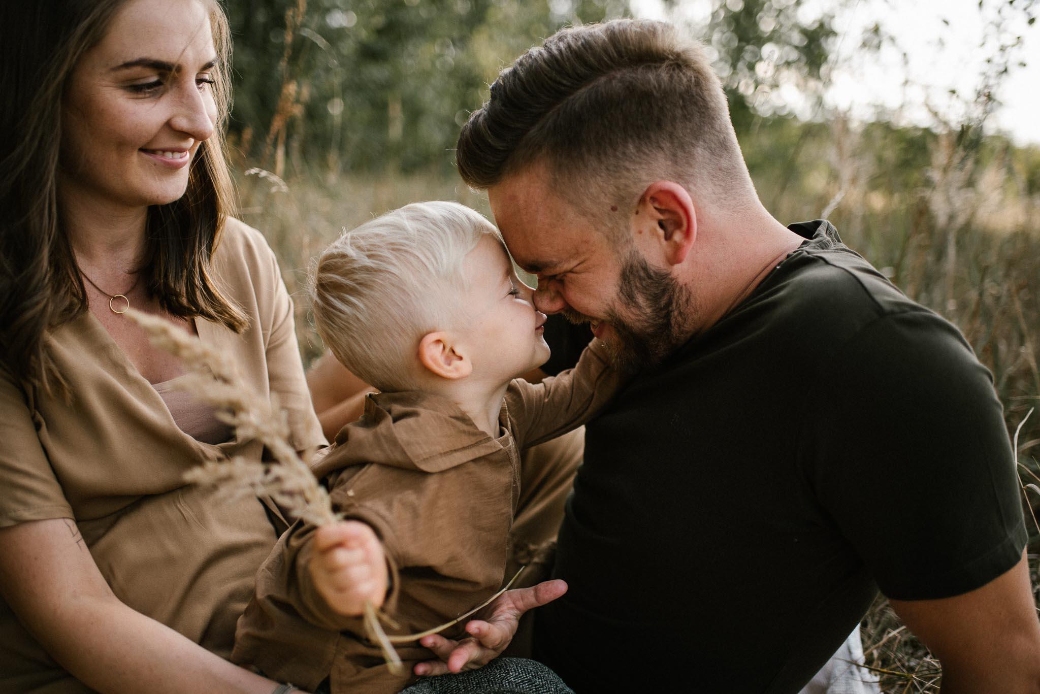 Chłopiec daje tacie buziaka - Sesja ciążowa na łące w plenerze Poznań