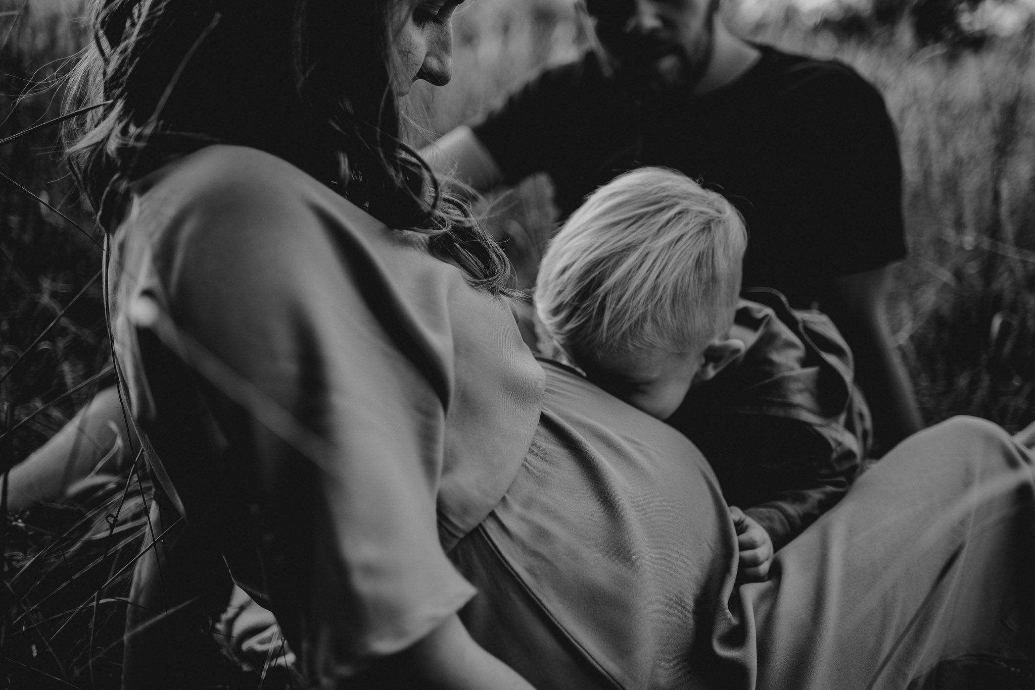 Chłopiec całuje ciążowy brzuch -Sesja ciążowa na łące w plenerze Poznań