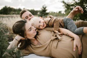 Rodzice bawią się z synkiem na kocu na łące - Sesja ciążowa na łące w plenerze Poznań