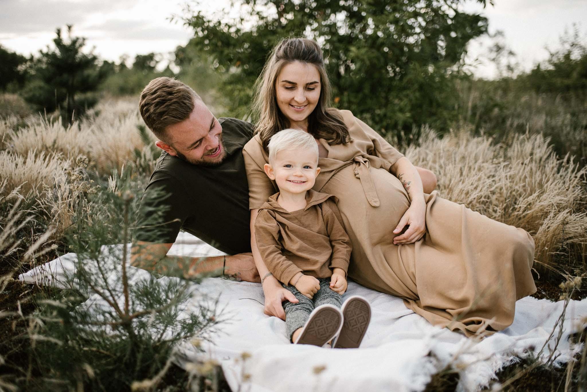 Rodzice z chłopcem na kocu na łące - Sesja ciążowa na łące w plenerze Poznań