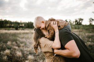 Tata trzyma chłopca na barana - Sesja ciążowa na łące w plenerze Poznań
