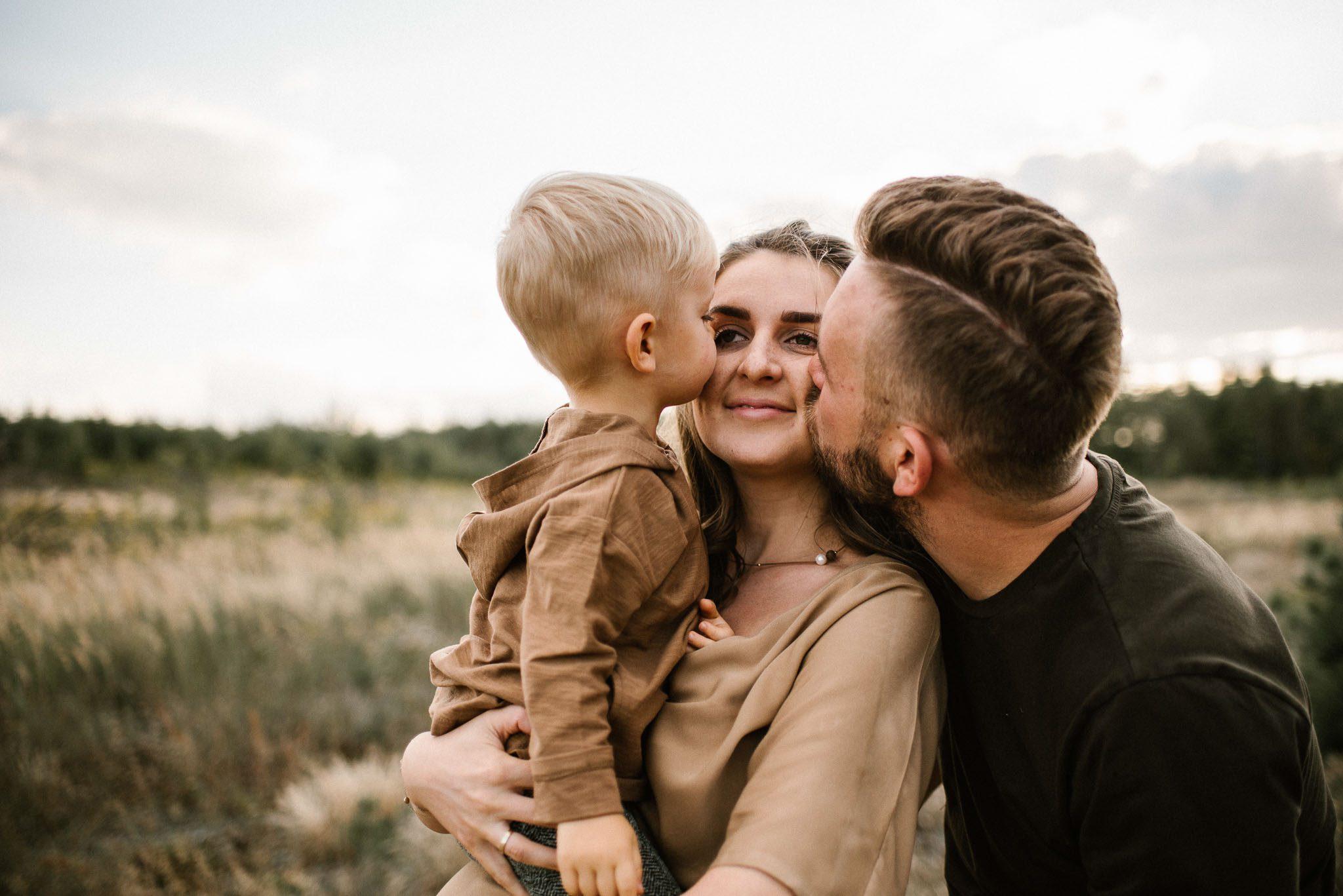 Mama trzyma chłopca na rękach - Sesja ciążowa na łące w plenerze Poznań
