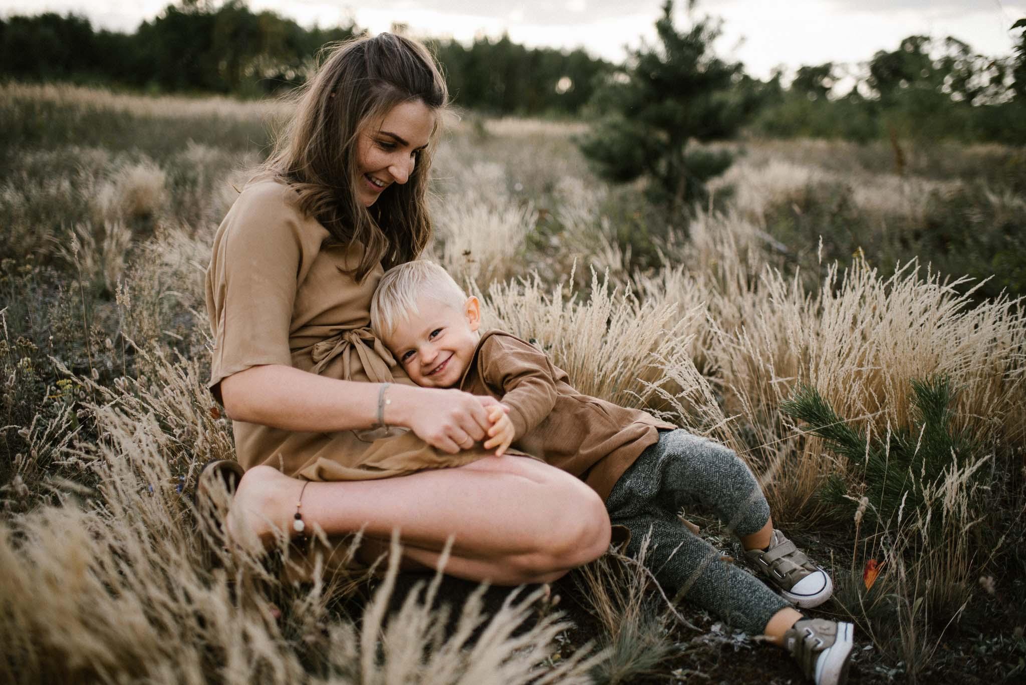 Chłopiec przytula się do mamy - Sesja ciążowa na łące w plenerze Poznań