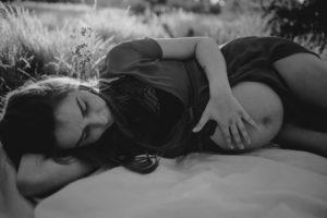 Kobieta z odsłoniętym brzuchem ciążowym na łące na kocu-Sesja ciążowa na polu w plenerze Poznań