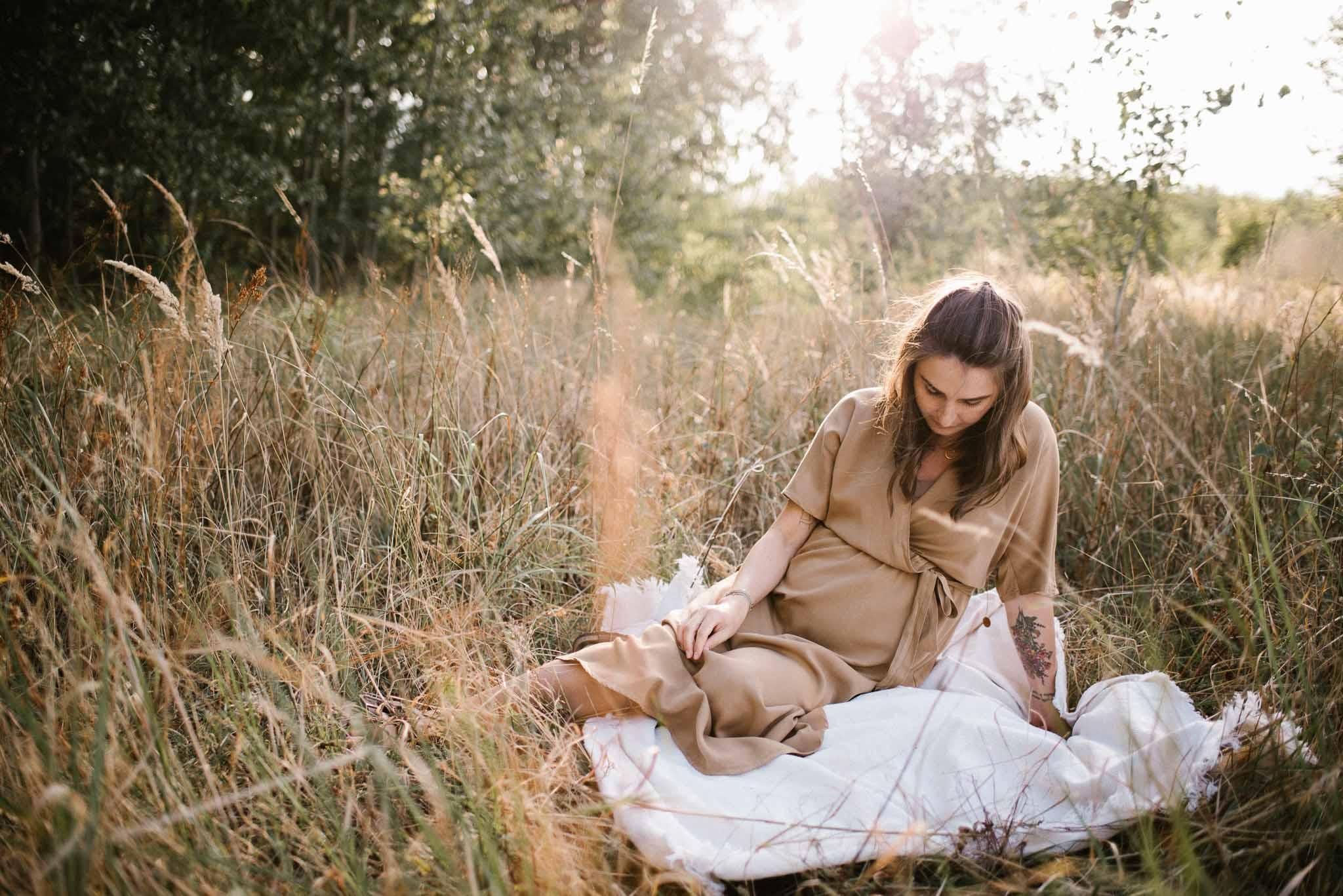Kobieta w ciąży na łące na kocu-Sesja ciążowa na polu w plenerze Poznań
