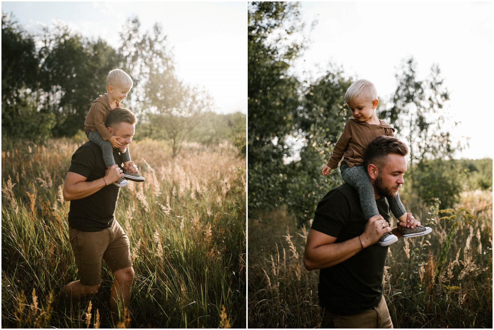 tata z synem na barana biegną przez łąkę - Sesja ciążowa na polu w plenerze Poznań