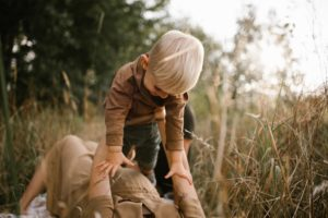 Synek u mamy na rękach na kocu - Sesja ciążowa na polu w plenerze Poznań