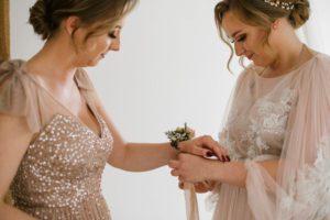 Panna młoda zakłada świadkowej kwiaty na rękę - sesja ślubna Biskupice Siedem Drzew