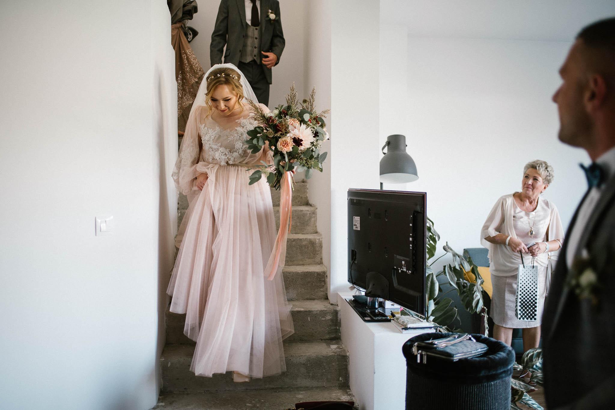 Panna młoda schodzi po schodach - sesja ślubna Biskupice Siedem Drzew