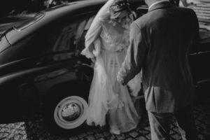 Panna młoda wysiada z bordowego samochodu - ślub w Biskupicach, Siedem Drzew
