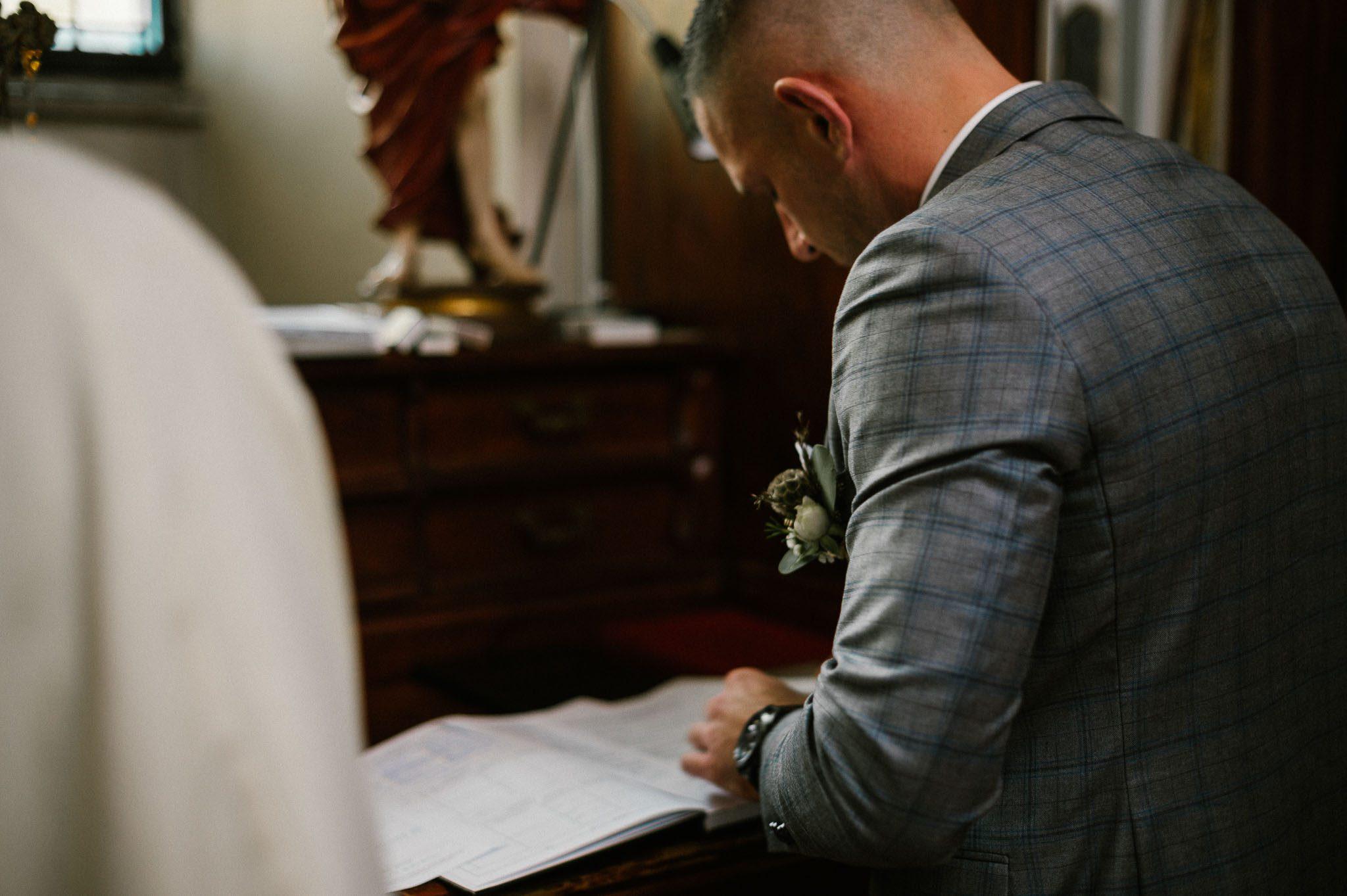 Pan młody podpisuje dokumenty w kościele - ślub w Biskupicach, Siedem Drzew