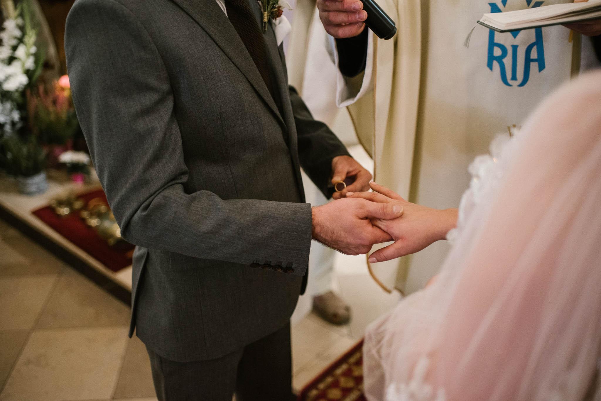 Pan młody zakłada żonie obrączkę - ślub w Biskupicach, Siedem Drzew